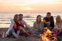 Group Of Young Friends Sitting By The Fire at beach