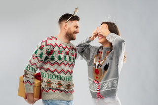 happy couple in christmas sweaters with gift box
