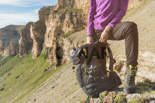 Smiling girl traveler in a yellow hat and a pair of sunglasses stands at the foot of epic rocks with a backpack next and looks away. View below chest