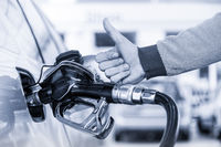 Petrol or gasoline being pumped into a motor vehicle car. Closeup of man, showing thumb up gesture, pumping gasoline fuel in car at gas station.