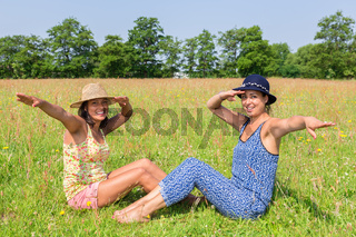 Two women with hats greeting in green pasture