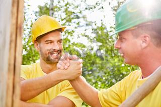 Zwei Bauarbeiter schütteln sich die Hände