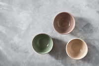 Three colorful porcelain bowls isolated on stone gray background, flat lay