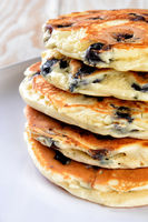 A stack of fresh homemade blueberry pancakes on white plate