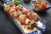 Traditional Greek souvlaki barbecue skewer with  tomato onion salad and paprika as closeup on a plate
