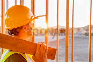 Female Construcion Worker Looking Out From New Home Framing
