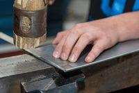 Handwerker falzt Blechkanten mit Holzhammer - Nahaufnahme