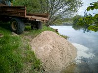 Tractor trailer tipping a load of sand to create beach