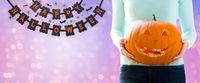 close up of woman holding halloween pumpkin