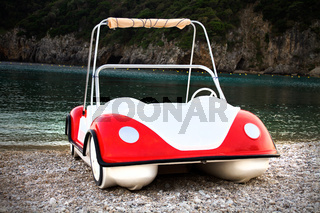 Water Vehicle in the Form of Buggy Car Parked  on Coarse Sand. Crystal Clear Water and Verdant Rock Formation in the Background. Travel Destination Ideas.