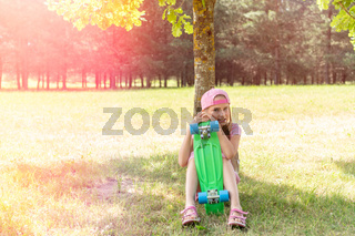 Girl with skateboard in a summer park