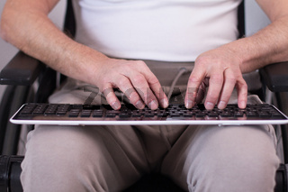 Disabled man typing on keyboard.