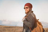 Hipster young man with beard and mustache wearing sunglasses posing against the background of mountains