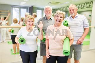 Glückliche Senioren mit Yogamatten im Sportstudio