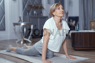 Mature woman stands in upward-facing dog pose