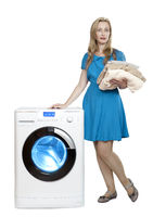 beautiful woman in a blue dress next to a new washing machine holds a stack of clean laundry