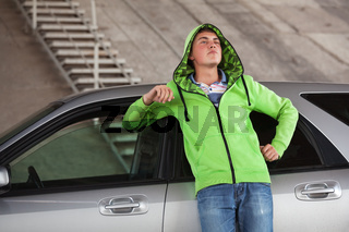 Sad young man in depression standing next to his car outdoor