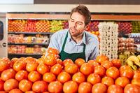 Verkäufer sortiert Tomaten in der Gemüseabteilung