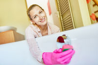 Hausfrau als Putzfrau reinigt die Badewanne