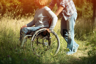 Man pushes the wheelchair with his girlfriend,