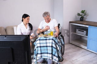 Nurse bringing food to patient in wheelchair.