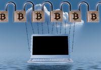 Chain of brass padlocks to illustrate blockchain above laptop