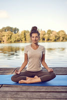 Smiling woman sitting meditating on a wooden deck