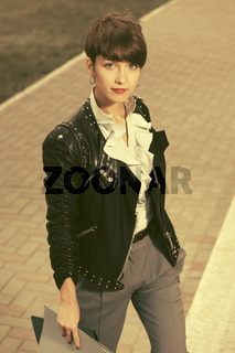 Happy young fashion business woman in leather jacket with file folder