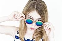 Cute girl in green sunglasses on white