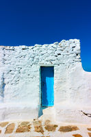 Narrow door in ancient whitewashed wall
