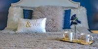 Couple bed with pillows and mugs on a tray