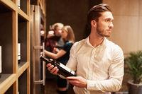 Mann mit einer Flasche Rotwein vor einem Regal
