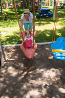 mother and daughter swinging in the park