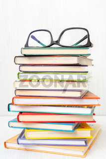 Stack of books with a eyeglasses on top