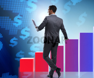 Businessman standing next to bar chart in business concept