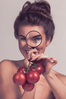 Girl inspecting tomato with magnifying glass