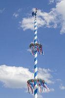 Bayrischer Maibaum vor weissblauem Wolkenhimmel
