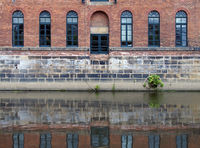 an old brick canal warehouse in leeds with windows reflected in the water