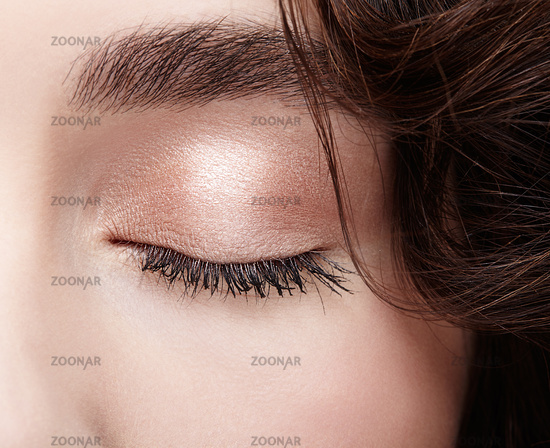 Closeup macro shot of closed female eye. Woman eye with nude makeup and long lashes