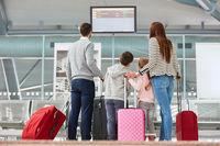 Familie schaut auf die Anzeigetafel im Flughafen Terminal
