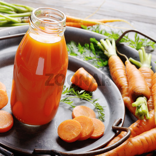 Vegetarian background of old tray with carrots and small bottle of juice on slate stone