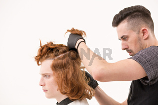 Barber pinning a hair of his client with a hairpin