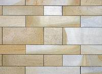 full frame image of a wall made of large flat blocks of textured yellow and grey york stone