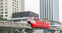 Red monorail train against of modern city in background