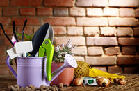 Gardening tools of shovel rake labels and watering can on wooden table