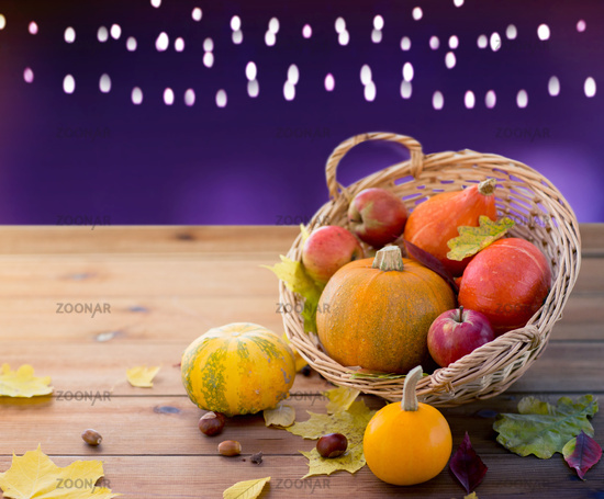 close up of pumpkins in basket on wooden table
