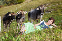 Woman in dirndl is before their cows in the grass