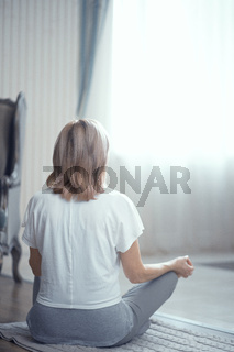 An Adult Woman Meditates After Doing Yoga at Home in the Living Room.