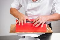Professional confectioner making delicious red cake, close up.
