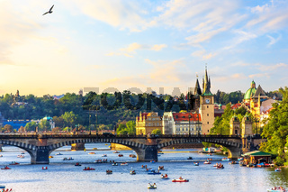 The Vltava River in Prague with people floating on paddleboats n